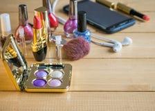 Grande insieme dei cosmetici, del telefono cellulare e delle cuffie su una tavola di legno Fotografia Stock