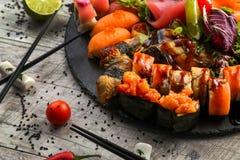 Grande insieme dei sushi, la mano che tiene i bastoncini, la vista dalla cima Fotografie Stock Libere da Diritti