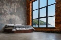 Grande interno del sottotetto con il letto ed il mare e montagne nella finestra immagini stock