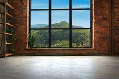 Grande interno del sottotetto con le montagne nella finestra fotografia stock