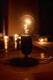 Grande lampe à incandescence électrique balayée sur le plancher, sur un fond foncé Lumière dans la densité Image libre de droits