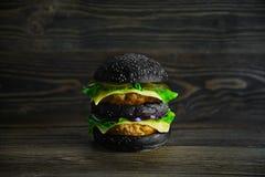 Grande mackintosh nero con gli ortaggi freschi e la cotoletta succosa Fotografie Stock
