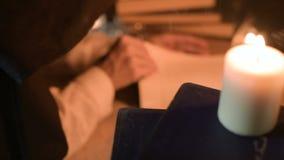 Grande magicienne en gros plan de fille dans une chambre noire avec la lueur d'une bougie recherchant un charme dans un livre Cam banque de vidéos