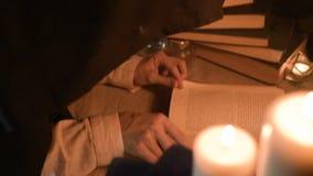 Grande magicienne en gros plan de fille dans une chambre noire avec la lueur d'une bougie recherchant un charme dans un livre Cam clips vidéos
