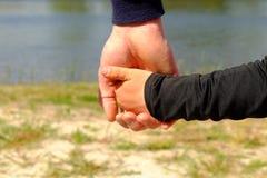 Grande main de prise de la main du père d'un peu d'enfant Mains dans des chemises bleues et noires photos stock