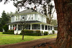 Grande maison de pays avec l'enrouler large autour du porche photographie stock