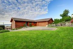 Grande maison en bois d'équilibre avec le passage couvert et les un bon nombre d'herbe Photos libres de droits