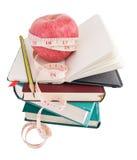 Grande mela matura con nastro adesivo di misura sul mucchio dei libri Fotografia Stock