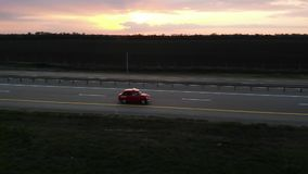 Grande metragem aérea da movimentação retro pequena vermelha do carro na estrada de 4 pistas no por do sol ou no nascer do sol co video estoque