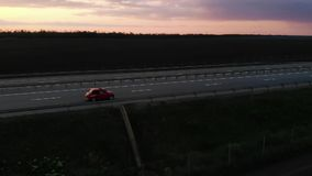 Grande metragem aérea da movimentação retro pequena vermelha do carro na estrada de 4 pistas no por do sol ou no nascer do sol co vídeos de arquivo