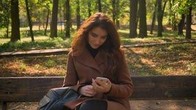Grande metragem do assento em uma menina moreno caucasiano do banco no ar livre agradável ensolarado do parque e de apreciar a na video estoque