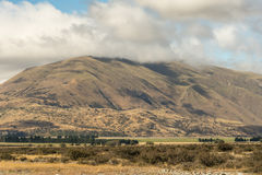 Grande montagna in nuvole alla roccia media della terra, Nuova Zelanda Immagini Stock