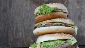 Grande montagne de l'hamburger trois juteux délicieux avec la vue haute étroite de laitue et de fromage Mensonge un d'hamburgers  banque de vidéos