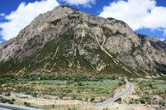 Grande montagne et petit village Image libre de droits