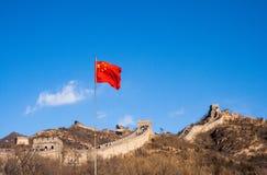 Grande Muralha de China com a bandeira chinesa que acena contra um céu azul imagens de stock