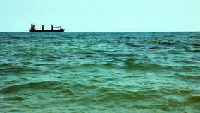 Grande nave da carico alla linea di orizzonte in oceano aperto stock footage