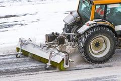 Grande neve que ara a máquina do trator no trabalho na estrada durante uma tempestade da neve no inverno imagem de stock