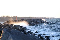 Grande onda que bate a rocha no por do sol foto de stock