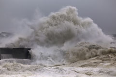 Grande onda tempestosa che si rompe sopra il pilastro Fotografie Stock