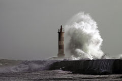 Grande onde contre le phare photographie stock libre de droits