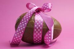 Grande ovo da páscoa do chocolate com a fita cor-de-rosa do às bolinhas Imagens de Stock Royalty Free