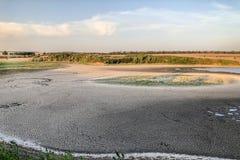 Grande paesaggio con la riva ed il cielo blu incrinati asciutti del lago della terra Terreno di siccità Paesaggio fantastico inso fotografia stock