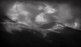 Grande paesaggio della montagna con un villaggio nella distanza, in un'interpretazione in bianco e nero Immagini Stock