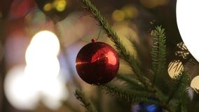 Grande palla rossa brillante che appende su un albero di Natale nei precedenti Primo piano stock footage