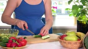 Grande pancia della donna incinta e delle mani che tagliano cetriolo sul tavolo da cucina stock footage