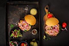 Grande panino - hamburger dell'hamburger con manzo, il pomodoro, il cetriolo marinato ed il bacon fritto immagini stock libere da diritti