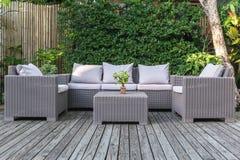 Grande patio del terrazzo con i mobili da giardino del rattan nel giardino sul pavimento di legno fotografia stock