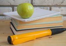 Grande penna del ricordo di Apple sui libri e sui taccuini, studio di concetto Fotografie Stock