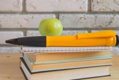 Grande penna del ricordo di Apple sui libri e sui taccuini, studio di concetto Fotografia Stock