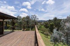 Grande piattaforma di legno vicino alla casa con il paesaggio della molla immagini stock
