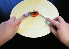 Grande piatto con un piccolo pezzo di mani della donna e dell'alimento fotografie stock libere da diritti