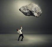 Grande pietra che cade giù sull'uomo d'affari spaventato fotografia stock libera da diritti