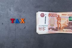 Grande pila di banconote russe dei soldi di cinque mila rubli che si trovano su un fondo grigio del cemento fotografia stock
