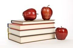 Grande pila di libri e di mele rosse su fondo bianco immagini stock