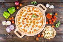 """Grande pizza """"margarita """"avec la planche à découper ronde de fromage et de tomates sur un fond en bois foncé ingrédients photos stock"""