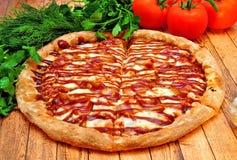 Grande pizza avec un barbecue sur une table en bois images stock