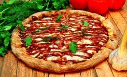 Grande pizza avec un barbecue sur une table en bois photos libres de droits