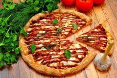Grande pizza con un barbecue su una tavola di legno Fotografie Stock