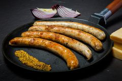 Grande po?le avec les saucisses minces frites et la moutarde granulaire photographie stock