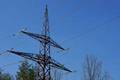 Grande polo preto do ferro com fios contra o céu e os ramos imagem de stock