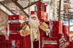 Grande poupée gaie Santa Claus de Santa Claus et beaucoup de boîte-cadeau rouges avec des rubans et sur le fond brillant Noël Images libres de droits