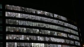 Grande prédio de escritórios na noite Janelas iluminadas Os povos terminam o trabalho Vista da parte inferior video estoque