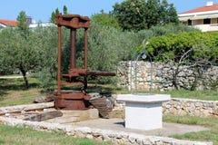 Grande presse rouillée d'huile d'olive de cru en métal rétro montée en machine sur la base concrète à côté du puits nouvellement  photos libres de droits