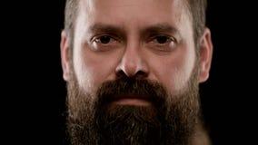 Grande primo piano del fronte duro di un uomo adulto barbuto con gli occhi marroni archivi video
