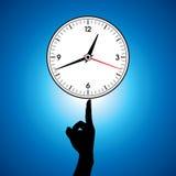 Grande prise blanche d'horloge murale dans un doigt Photo stock