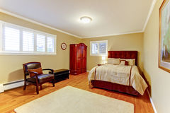 Grande quarto de hóspedes acolhedor com a cama e a armadura do marrom da camurça, os assoalhos de folhosa e paredes bege Fotografia de Stock
